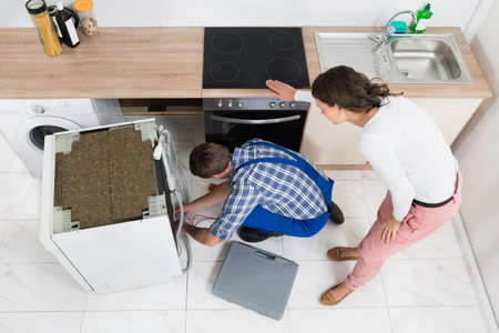 Young Woman Looking At The Work Of Repairman Repairing Dishwasher In Kitchen
