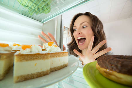 Excited Young Woman Looking At Cake In Refrigerator At Home Фото со стока