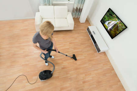 cleaning service: Young Woman Cleaning Floor With Vacuum Cleaner At Home Stock Photo