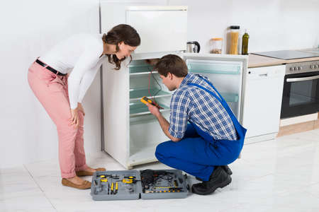 refrigerator kitchen: Beautiful Housewife Looking At Male Worker Repairing Refrigerator In Kitchen Room Stock Photo