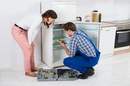 gospodarstwo domowe: Piękne Gospodyni Patrząc Na Mężczyzna Pracownik naprawy lodówka w kuchni pokoju
