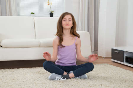 meditation room: Girl In Sportswear Doing Meditation In Living Room