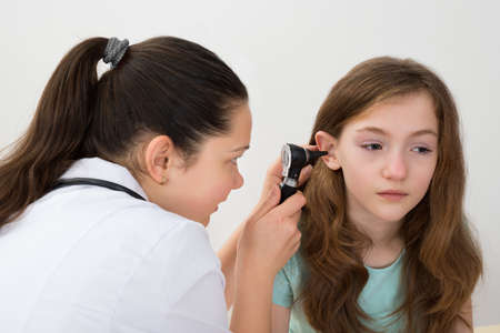 human ear: Female Doctor Examining Patient Ear With Otoscope In Clinic Stock Photo