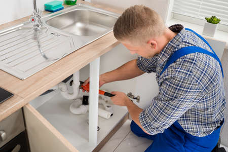 Male Plumber Fixing Sink Pipe With Adjustable Wrench In Kitchen Stock Photo - 43306834