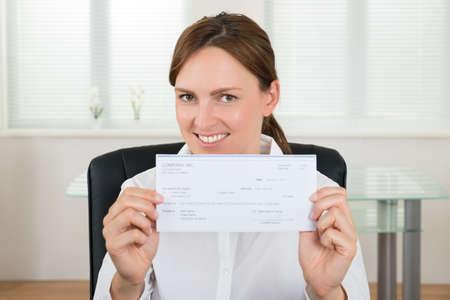 chequera: Retrato de mujer de negocios Mostrando Cheque En Office Foto de archivo