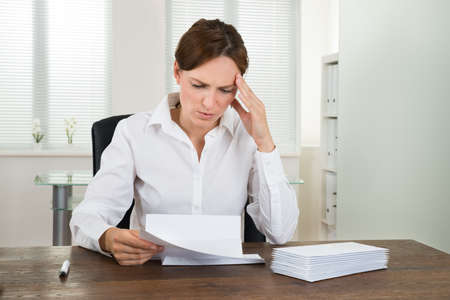 work stress: Stressed Businesswoman Looking At Document At Desk In Office