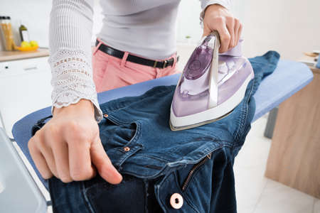 Close-up Of Woman Ironing Jeans On Ironing Board Stock Photo