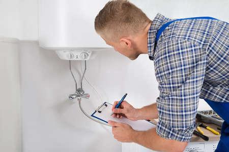 fontanero: Hombre fontanero escrito en el portapapeles delante de Calentador eléctrico en cocina Sala Foto de archivo