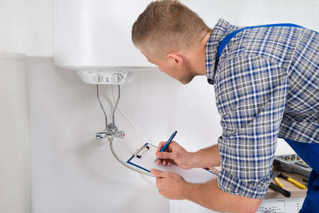 Male Plumber Writing On Clipboard In Front Of Electric Boiler In Kitchen Room
