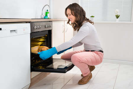 oven chicken: Beautiful Young Woman Wearing Gloves Cooking Chicken In Oven Stock Photo