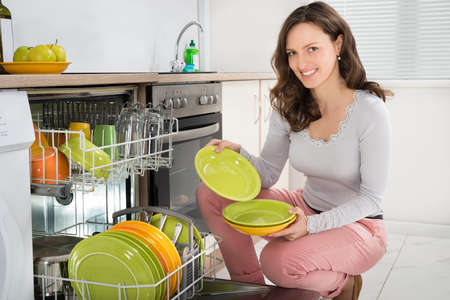 Young Happy Woman Arranging Plates In Dishwasher At Home