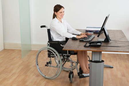 paraplegic: Feliz Empresaria que se sienta en silla de ruedas mientras que trabaja en equipo en el escritorio