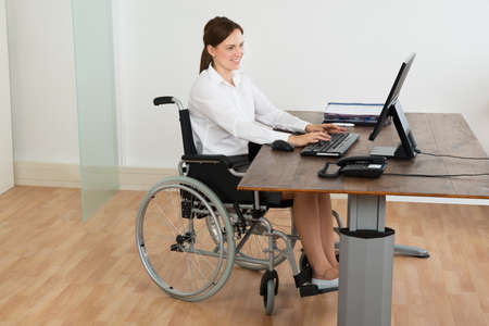 1 person: Happy Businesswoman Sitting On Wheelchair While Working On Computer At Desk
