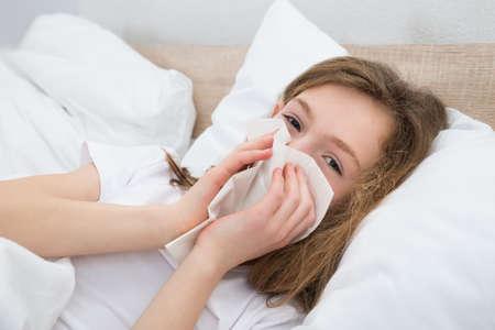 chory: Na łóżku chorej Kichanie W Chusteczka w sypialni Zdjęcie Seryjne