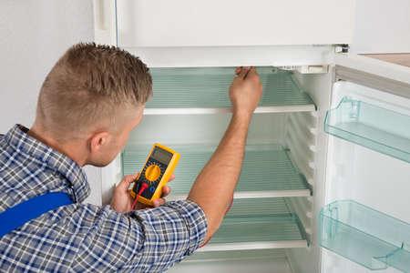 refrigerador: Joven Hombre Técnico Comprobación nevera con multímetro digital