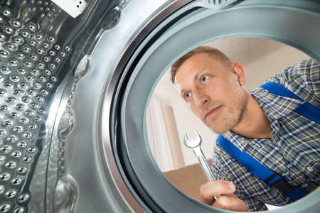 Young Repairman With Spanner Looking Inside The Washing Machine