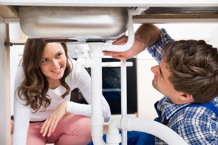 fontanero: Joven mujer feliz que mira Como trabajador en virtud de Trabajo El fregadero de cocina