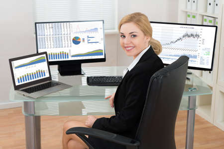 computers office: Happy Businesswoman On Office Chair With Computers Display Showing Graphs At Desk