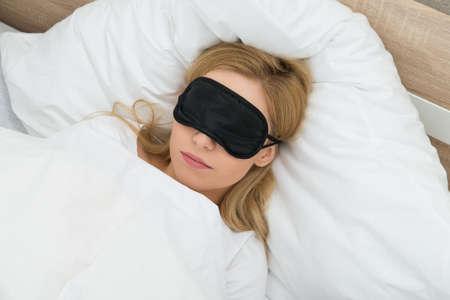 Mujer joven que duerme con la máscara del sueño en el dormitorio