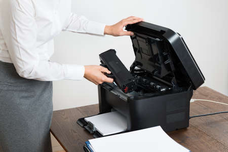 toner: Close-up Of Businesswoman Inserting Laser Cartridge In Printer Stock Photo