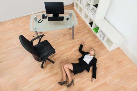 exhausted: High Angle View Of Young Businesswoman Fainted On Floor In Office
