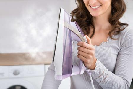 スチーム アイロンを手で押しながら笑みを浮かべて女性をクローズ アップ 写真素材