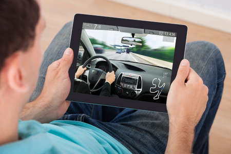 gibier: Jeune homme jouant Car Racing Game On tablette num�rique � la maison