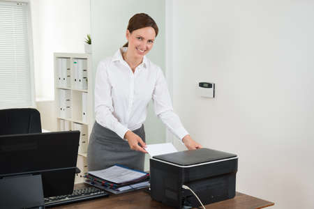 Young Female Secretary Inserting Paper In Printer At Desk