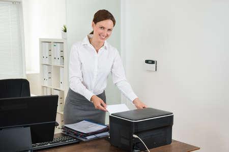 젊은 여성 장관은 책상에 프린터에서 종이를 삽입 스톡 콘텐츠