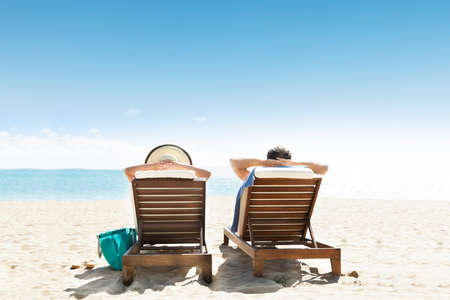 sunbed: Young Couple Lying On Lounge Chair At The Beach Stock Photo