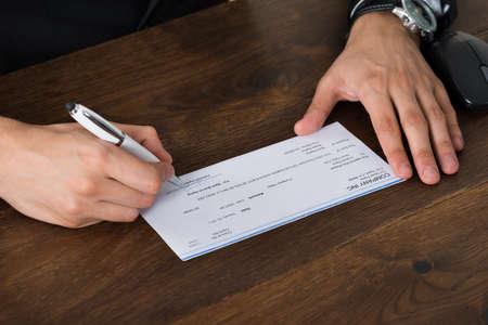 chequera: Primer plano de la persona Manos con la pluma de firma de cheques en el escritorio