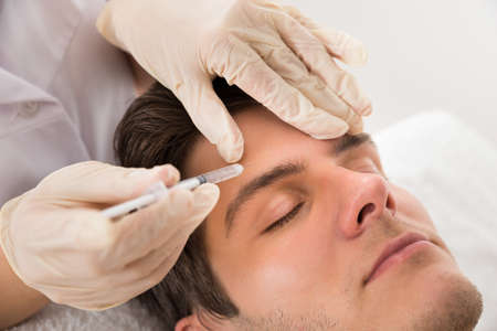 plastic glove: Young Man Having Botox Treatment At Beauty Clinic Stock Photo