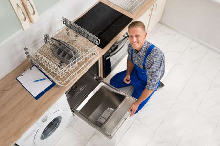 kitchen appliances: High Angle View Of Male Worker With Toolbox Repairing Dishwasher In Kitchen Room