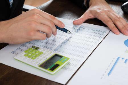 accounting: Primer De Empresario de Trabajo Con Contabilidad Documento En El Escritorio Foto de archivo