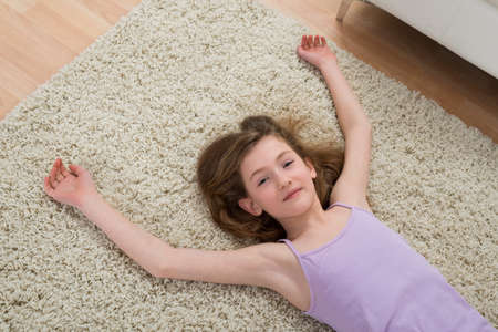 children sport: High Angle View Of Girl Resting On Carpet After Workout At Home