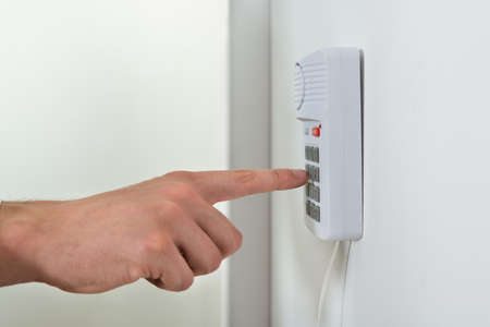 home security: Close-up Of Person Hand Pressing Button On Door Security System Stock Photo