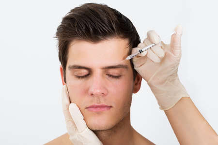 inyeccion: Primer plano de la persona Manos inyección de la jeringuilla con Botox para el tratamiento de la cara Foto de archivo