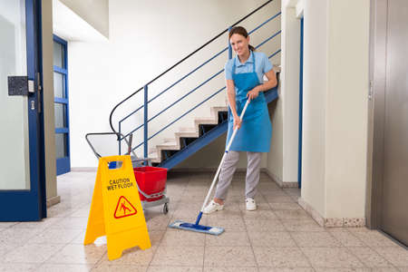 cleaning an office: Young Happy Female Worker With Cleaning Equipments And Wet Floor Sign On Floor