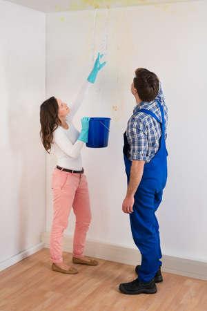 Jeune femme avec seau Afficher une fuite d'eau au plafond Dommages Pour Maintenance Guy Banque d'images - 43306262