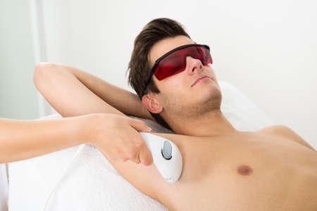pulizia viso: Close-up Di mani di persona Dare Laser Epilazione terapia ad un giovane uomo