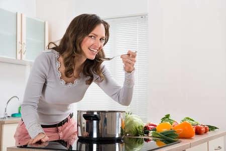 Giovane donna sorridente mentre degustazione pasto dal utensili in cucina moderna Archivio Fotografico - 43306265