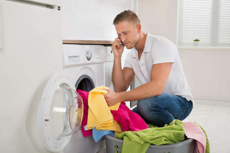 man laundry: Young Man Talking On Mobile Phone While Putting Laundry In Washing Machine Stock Photo