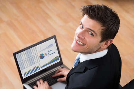 analyzing: Young Happy Businessman Analyzing Statistical Data On Laptop In Office Stock Photo