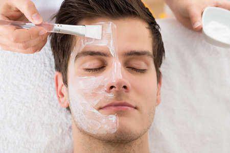 facial cream: Therapist Hands With Brush Applying Face Mask To A Young Man In A Spa Stock Photo
