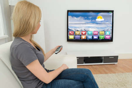 tv: Jeune femme sur la télécommande Canapé Tenir devant la télévision avec les applications