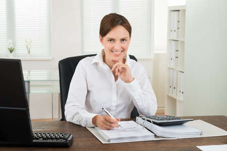 Photo Of Happy Businesswoman Calculating Invoice At Desk