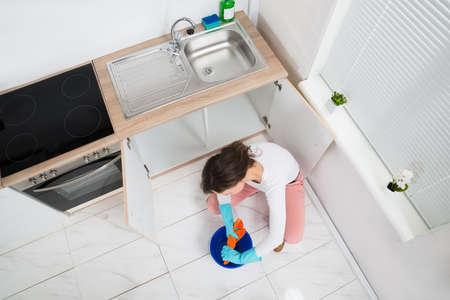 servicio domestico: Joven mujer que exprime Wet Trapo En Azul Cubo En La Cocina Sala