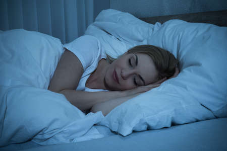 bed sheet: Young Woman With Blanket Sleeping At Night In Bed Stock Photo