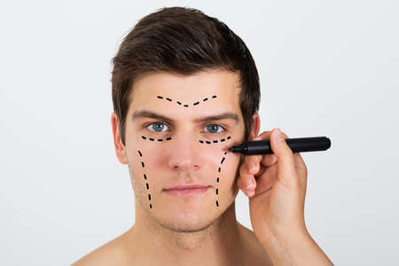cosmeticos: Primer plano de la persona Manos que hacen Líneas Con La Pluma En La Cara Del Hombre Joven