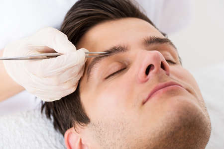 eyebrow: Close-up Of Beautician Hands Plucking Handsome Man Eyebrows With Tweezers Stock Photo